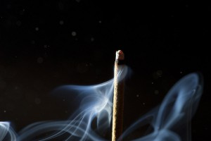 glühendes Räucherstäbchen auf schwarzem Hintergrund mit blauem Rauch