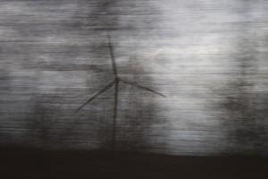 Windrad hinter verschwommenen Bäumen